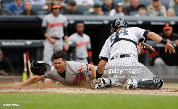Breyvic Valera of the Baltimore Orioles is tagged out at the plate during the fifth inning by Gary Sanchez of the New York Yankees at Yankee Stadium...