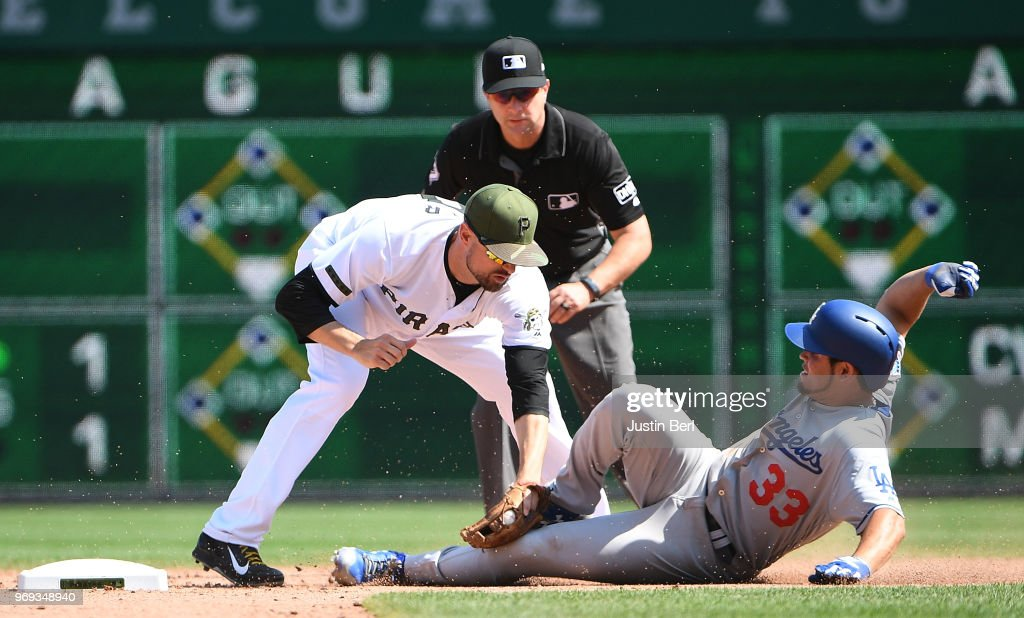 Breyvic Valera #33 of the Los Angeles Dodgers is tagged out at second base by Jordy Mercer #10 of the Pittsburgh Pirates while attempting to advance in the ninth inning during the game at PNC Park on June 7, 2018 in Pittsburgh, Pennsylvania.