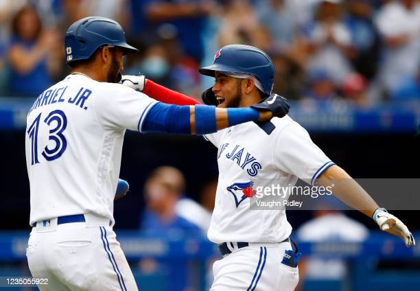 Breyvic Valera of the Toronto Blue Jays celebrates with Lourdes Gurriel Jr. #13 after hitting a home run in the fourth inning during a MLB game...