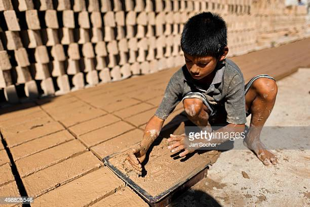 Brian a tenyearold Salvadoran boy works at a brick factory on December 21 2013 in Istahua El Salvador Child labour is a common practice at the...