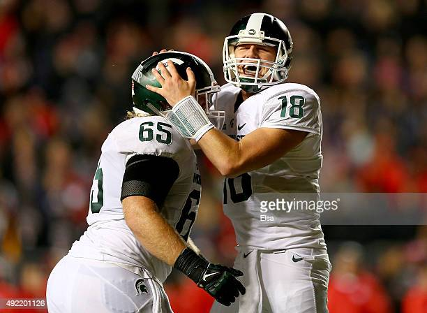 Brian Allen and Connor Cook of the Michigan State Spartans celebrate a touchdown by teammate LJ Scott in the fourth quarter against the Rutgers...