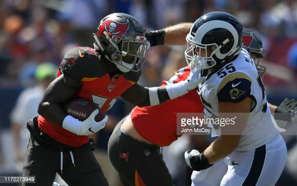 Brian Allen of the Los Angeles Rams tries to tackle Jordan Whitehead of the Tampa Bay Buccaneers after he intercepted the ball in the second quarter...