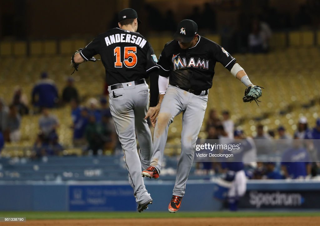 Brian Anderson #15 and Miguel Rojas #19 of the Miami Marlins celebrate after their 8-6 win against the Los Angeles Dodgers in the MLB game at Dodger Stadium on April 25, 2018 in Los Angeles, California.