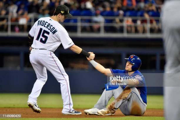 Brian Anderson of the Miami Marlins helps up JD Davis of the New York Mets after an inning ending double play in the seventh inning of the game at...