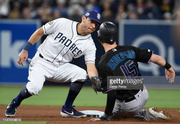 Brian Anderson of the Miami Marlins is tagged by Ian Kinsler of the San Diego Padres as he tries to steal second base during the seventh inning of a...