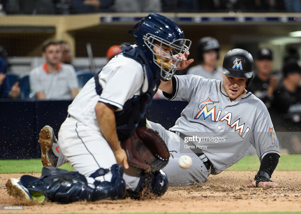 Brian Anderson #15 of the Miami Marlins scores ahead of the throw to Raffy Lopez #0 of the San Diego Padres during the sixth inning of a baseball game at PETCO Park on May 29, 2018 in San Diego, California.