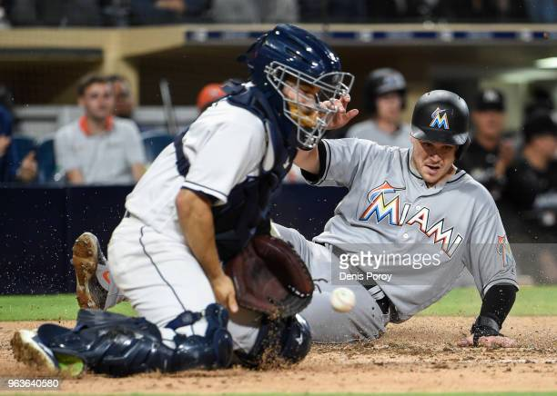 Brian Anderson of the Miami Marlins scores ahead of the throw to Raffy Lopez of the San Diego Padres during the sixth inning of a baseball game at...
