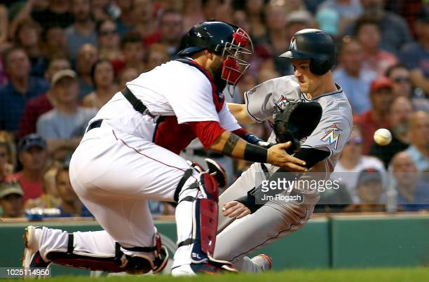 Brian Anderson of the Miami Marlins scores as Sandy Leon of the Boston Red Sox fields a late throw in the third inning at Fenway Park on August 29...