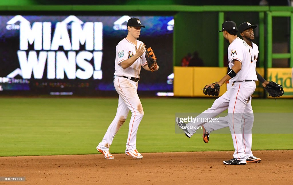 Brian Anderson #15, Yadiel Rivera #2, and Cameron Maybin #1 of the Miami Marlins celebrate the win after beating the Washington Nationals at Marlins Park on July 29, 2018 in Miami, Florida.