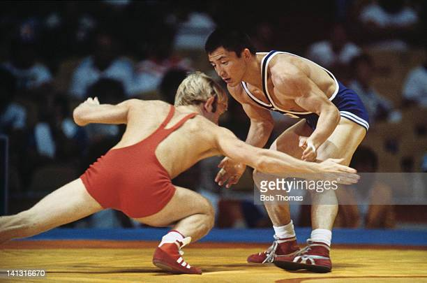 Brian Aspen of Great Britain competing in a Group A, Round Two match against Hideaki Tomiyama of Japan in the Men's Bantamweight, Freestyle Wrestling...
