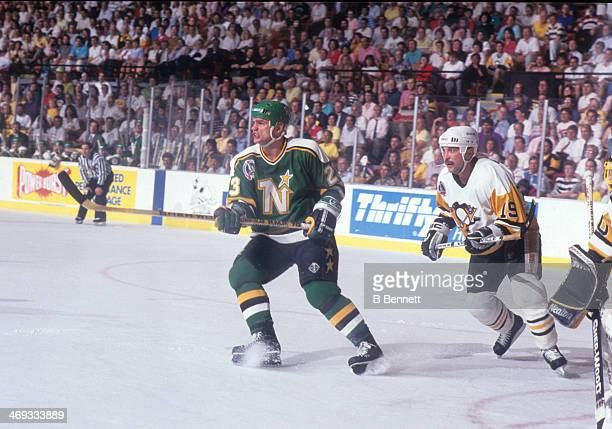 Brian Bellows of the Minnesota North Stars and Bryan Trottier of the Pittsburgh Penguins skate in front of the net during Game 5 of the 1991 Stanley...