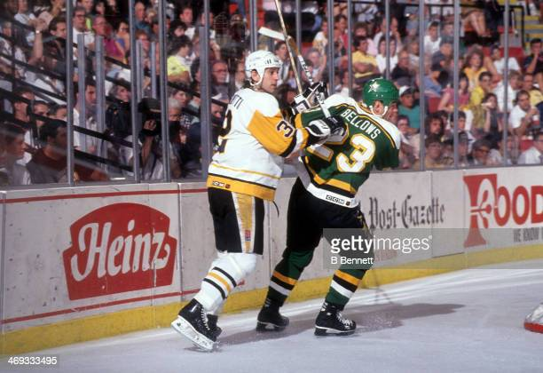 Brian Bellows of the Minnesota North Stars and Peter Taglianetti of the Pittsburgh Penguins skate behind the net during Game 5 of the 1991 Stanley...