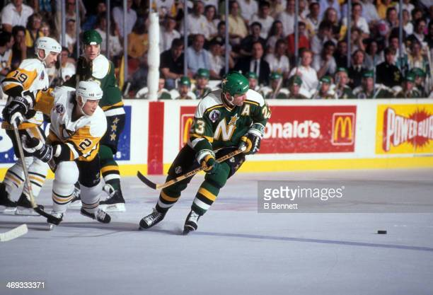 Brian Bellows of the Minnesota North Stars goes for the puck as Jim Paek of the Pittsburgh Penguins follows behind during Game 2 of the 1991 Stanley...