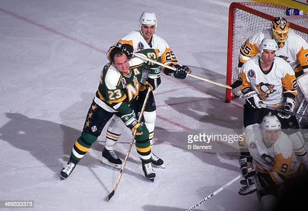 Brian Bellows of the Minnesota North Stars has his helmet knocked off as he battles for position with Kevin Stevens of the Pittsburgh Penguins during...