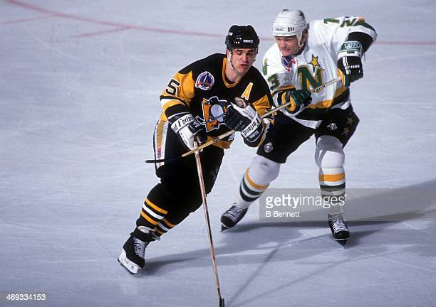 Brian Bellows of the Minnesota North Stars hooks Kevin Stevens of the Pittsburgh Penguins during Game 3 of the 1991 Stanley Cup Finals on May 19 1991...
