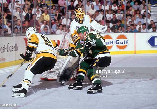 Brian Bellows of the Minnesota North Stars tries to hook Larry Murphy of the Pittsburgh Penguins as goalie Tom Barrasso of the Penguins tries to hook...