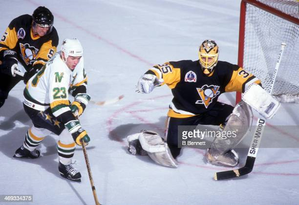 Brian Bellows of the Minnesota North Stars tries to shoot as he is hooked by Ulf Samuelsson of the Pittsburgh Penguins as goalie Tom Barrasso of the...