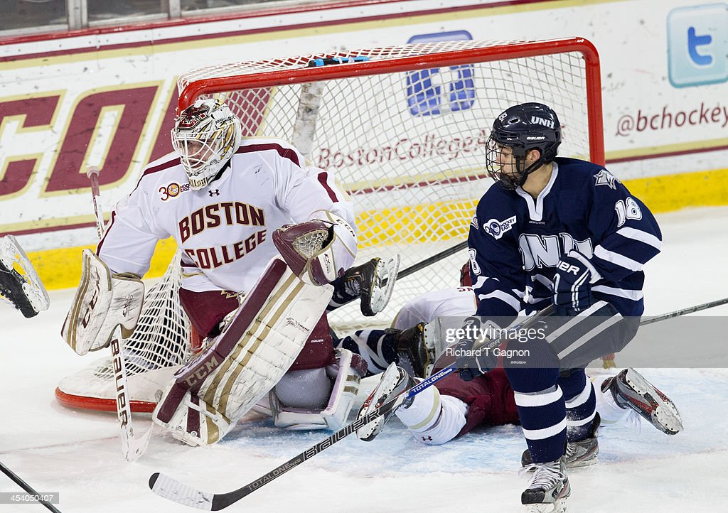 Brian Billett #1 of the Boston College Eagles and Jeff Silengo #18 of the New Hampshire Wildcats look for the puck during NCAA hockey action at Kelley Rink on December 6, 2013 in Chestnut Hill, Massachusetts.