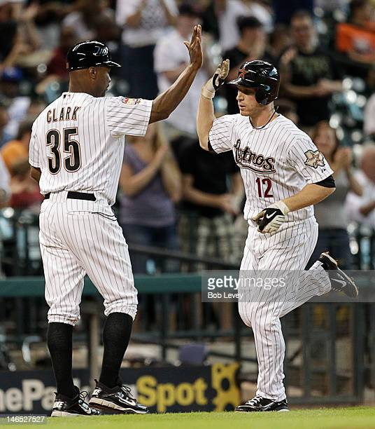 Brian Bixler of the Houston Astros receives a highfive from third base coach Dave Clark after hitting a home run in the first inning against the...