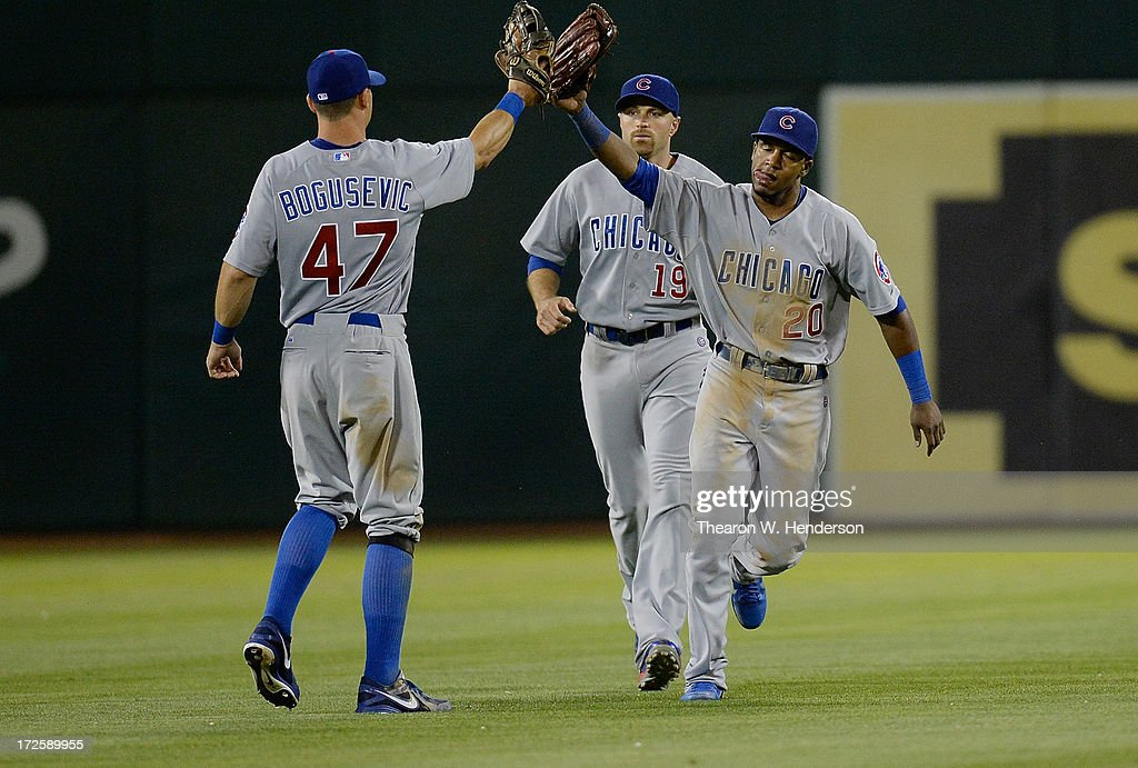 Brian Bogusevic #30, Julio Borbon #20 and Nate Schierholtz #19 of the Chicago Cubs celebrates defeating the Oakland Athletics 3-1 at O.co Coliseum on July 3, 2013 in Oakland, California.
