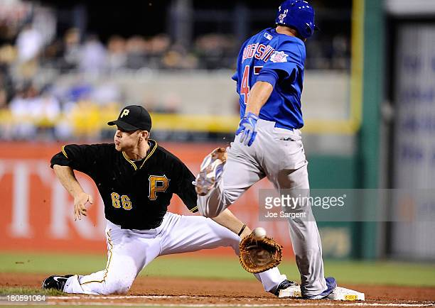 Brian Bogusevic of the Chicago Cubs is safe at first base in front of Justin Morneau of the Pittsburgh Pirates on September 14, 2013 at PNC Park in...