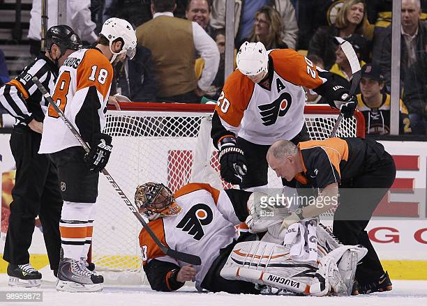 Brian Boucher of the Philadelphia Flyers attended to by teammates Chris Pronger and Mike Richards after he was injured in the second period against...