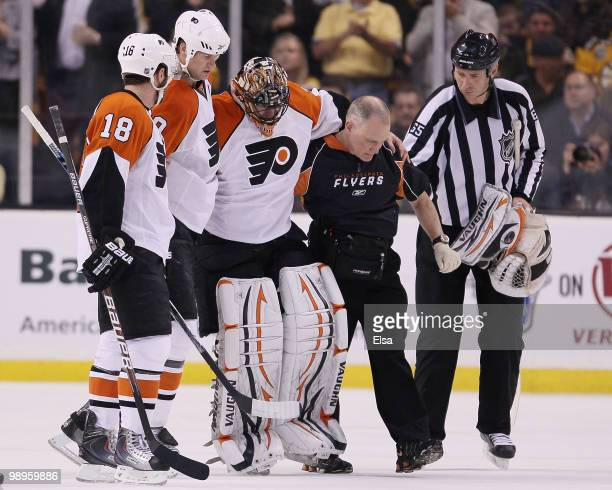 Brian Boucher of the Philadelphia Flyers is helped off the ice by teammates Chris Pronger and Mike Richards after he was injured in the second period...