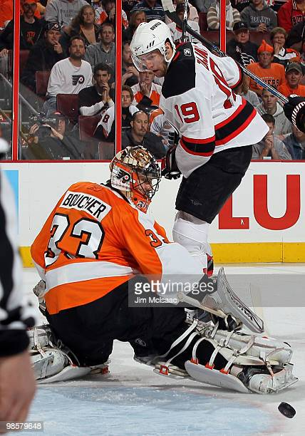 Brian Boucher of the Philadelphia Flyers makes a first period save under pressure from Travis Zajac of the New Jersey Devils in Game Four of the...