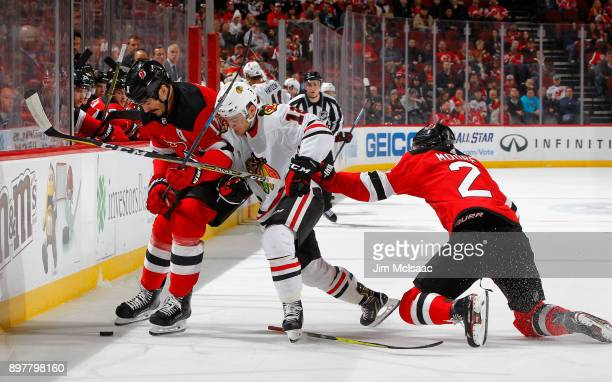 Brian Boyle and John Moore of the New Jersey Devils defend against Alex DeBrincat of the Chicago Blackhawks during the first period on December 23...