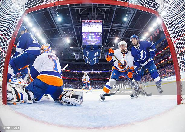 Brian Boyle and Tyler Johnson of the Tampa Bay Lightning battle against goalie Thomas Greiss and Calvin de Haan of the New York Islanders during the...
