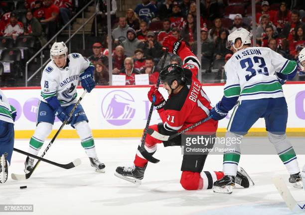 Brian Boyle of the New Jersey Devils and Henrik Sedin of the Vancouver Canucks watch as Jake Virtanen of the Vancouver Canucks controls the puck...