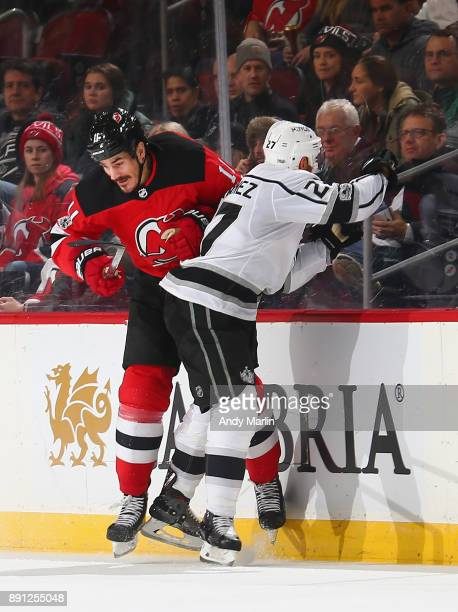Brian Boyle of the New Jersey Devils is checked into the boards by Alec Martinez of the Los Angeles Kings during the game at Prudential Center on...