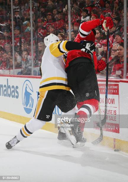 Brian Boyle of the New Jersey Devils is checked into the boards by Brian Dumoulin of the Pittsburgh Penguins during the game at Prudential Center on...