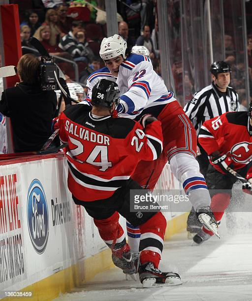 Brian Boyle of the New York Rangers hits Bryce Salvador of the New Jersey Devils during first period action at the Prudential Center on December 20,...