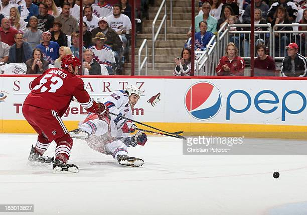 Brian Boyle of the New York Rangers shoots the puck as he falls to the ice defended by Derek Morris of the Phoenix Coyotes during the first period of...