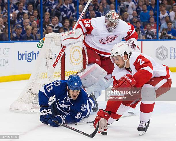 Brian Boyle of the Tampa Bay Lightning battles for the puck against Brendan Smith of the Detroit Red Wings after sliding into goalie Petr Mrazek...