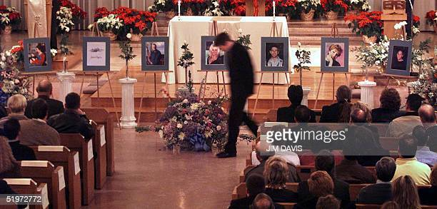 Brian Britney walks back to his seat after placing a flower next to the photograph of his partner Paul Marceau a victim of the Edgewater Technology...