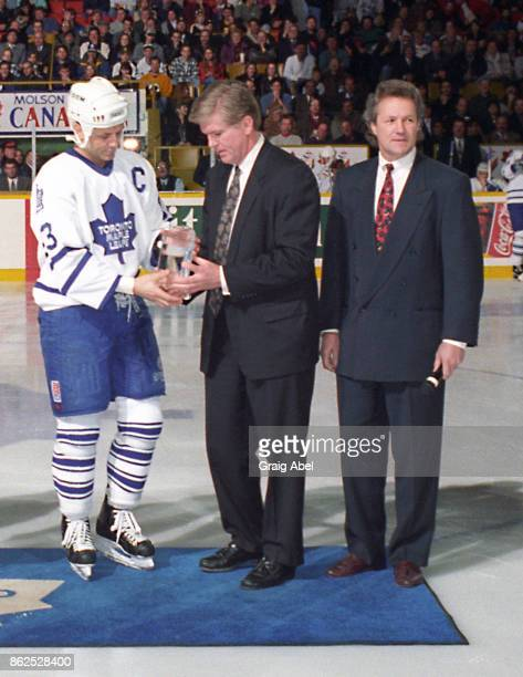 Brian Burke of the NHL and former Leaf Darryl Sittler present Doug Gilmour of the Toronto Maple Leafs with an award for achieving 1000 points prior...