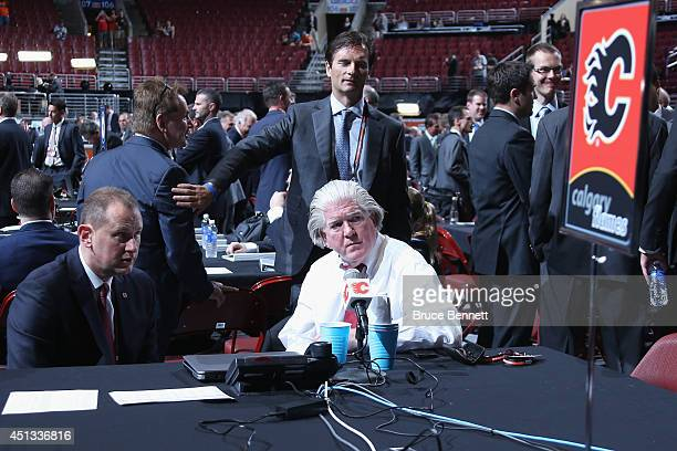 Brian Burke President of Hockey Operations for the Calgary Flames speaks with General Manager Brad Treliving prior to the first round of the 2014 NHL...