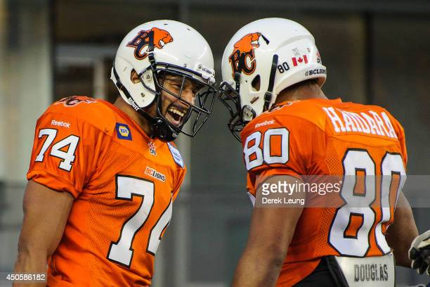 Brian Burnham and Seydou Junior Haidara of the BC Lions celebrate after a play against the Edmonton Eskimos during a CFL game at Commonwealth Stadium...