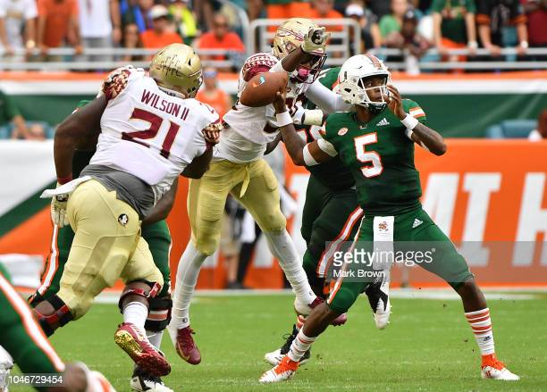 Brian Burns of the Florida State Seminoles causes a fumble by N'Kosi Perry of the Miami Hurricanes in the first half at Hard Rock Stadium on October...