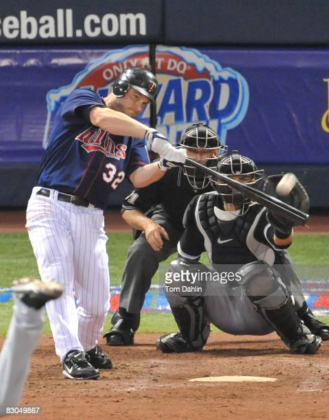 Brian Buscher of the Minnesota Twins connects with a pitch during an MLB game against the Chicago White Sox at the Hubert H. Humphrey Metrodome,...