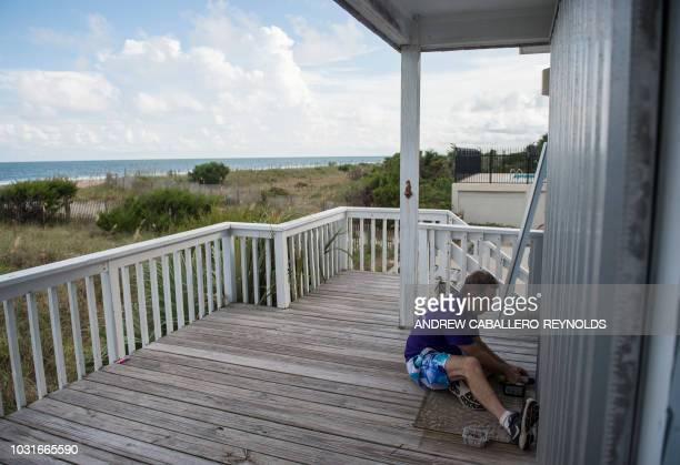 Brian Calahan helps seal a window on a beach house days before the arrival of Hurricane Florence at Wrightsville Beach North Carolina on September 11...