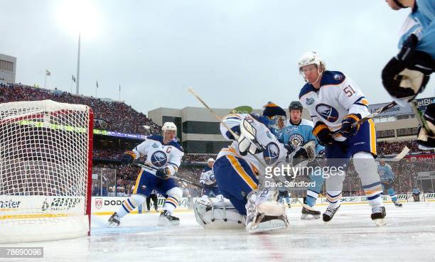 Brian Campbell and Ryan Miller of the Buffalo Sabres defend the net against Jordan Staal of the Pittsburgh Penguins during the NHL Winter Classic at...