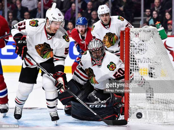 Brian Campbell of the Chicago Blackhawks and goaltender Corey Crawford watch the puck during the NHL game against the Montreal Canadiens at the Bell...