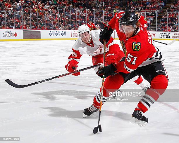 Brian Campbell of the Chicago Blackhawks controls the puck while Jan Mursak of the Detroit Red Wings pursues during an NHL game at Joe Louis Arena on...