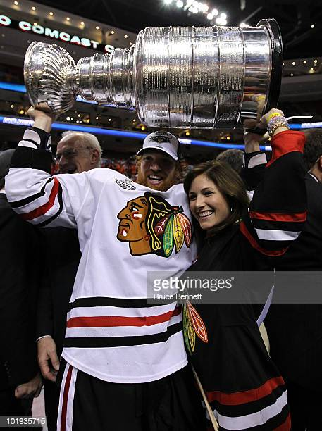 Brian Campbell of the Chicago Blackhawks hoists the Stanley Cup with his girlfriend after teammate Patrick Kane scored the gamewinning goal in...