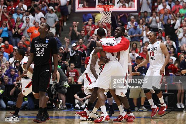 Brian Carlwell and Malcolm Thomas of the San Diego State Aztecs celebrate after defeating the Temple Owls 71 to 64 in double overtime during the...
