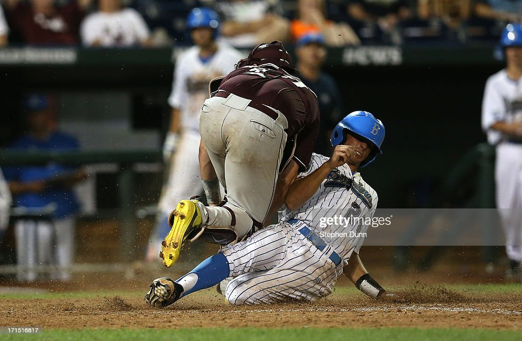 Brian Carroll #2 of the UCLA Bruins slides under catcher Nick Ammirati #17 to score a run in the eighth inning against the Mississippi State Bulldogs during game two of the College World Series Finals on June 25, 2013 at TD Ameritrade Park in Omaha, Nebraska.