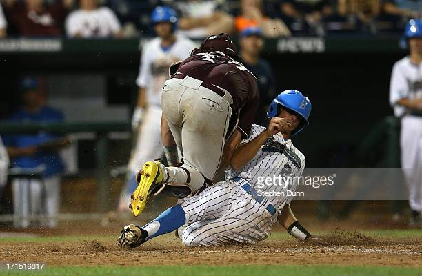 Brian Carroll of the UCLA Bruins slides under catcher Nick Ammirati to score a run in the eighth inning against the Mississippi State Bulldogs during...